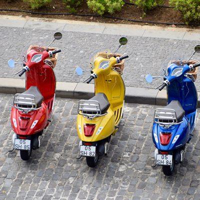 Sfeerbeeld van een rode, gele en blauwe eenpersoons scooter die langs de weg zijn geparkeerd. Ze hebben alledrie een rietenmandje voorop en staan met het stuur naar links gedraaid.