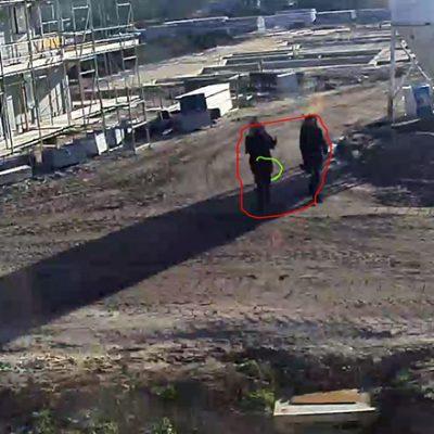 Sfeerbeeld van een screenshot van een beveiligingscamera die twee personen opneemt die op een bouwplaats lopen.