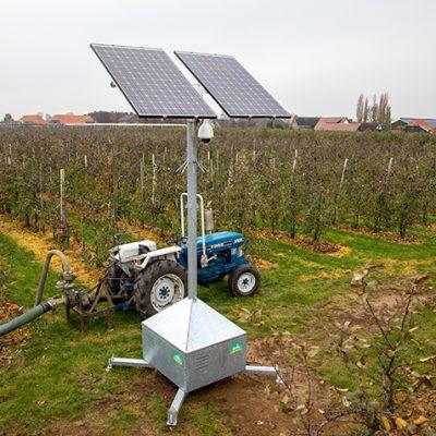Sfeerbeeld van objectbeveiliging met een mobiele cameramast in een boomgaard. Achter de mast staat een blauwe tractor die is aangesloten op de waterpompinstallatie.