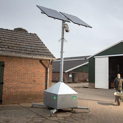 Sfeerbeeld van een boerenerf met drie schuren en voor de eerste staat een mobiele cameramast. De boer komt met een kruiwagen aanlopen.