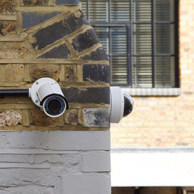 Sfeerbeeld van twee bewakingscamera's die op de hoek van gele stenen pand gemonteerd zijn. Ze wijzen ieder een andere kant op.