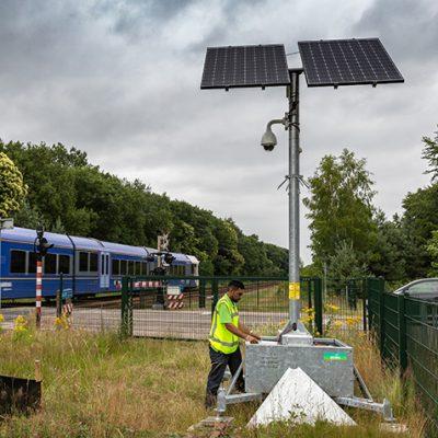 Sfeerbeeld van spoorwegveiligheid, want op de groenstrook langs het spoor staat bij een onbewaakte spoorwegovergang een mobiele cameramast voor toezicht. Er naast staat een man met een geel veiligheidsvestje onderhoudswerkzaamheden uit te voeren. Er komt ook een blauwe trein langsrijden en er staat een zwarte personenauto voor de slagbomen te wachten.