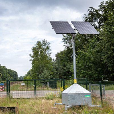Sfeerbeeld van een mobiele cameramast die op de groenstrook langs het spoor staat bij een onbewaakte spoorwegovergang.