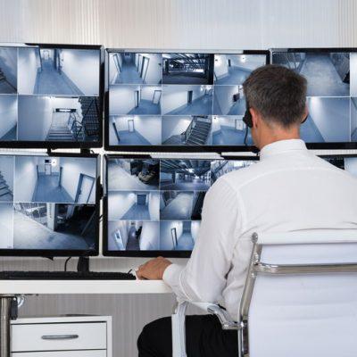 Sfeerbeeld van een man in een witte blouse die met een koptelefoon op meerdere monitors bekijkt waarop beelden van gangen en trapportalen te zien zijn.