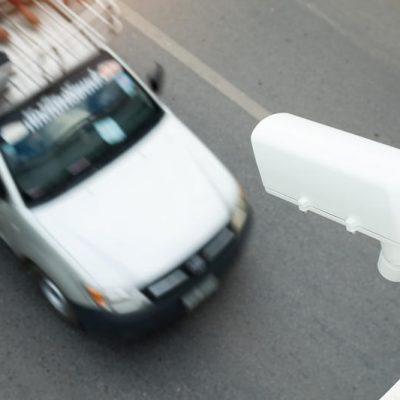 Sfeerbeeld van bovenaf een wegovergang genomen. Er rijdt een witte auto onder een verkeerscamera door.