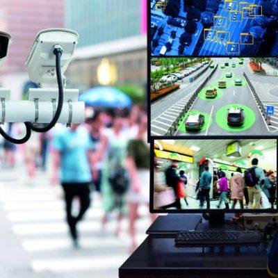 Sfeerbeeld van een bewaker achter meerdere monitors die verkeerssituaties observeerd.