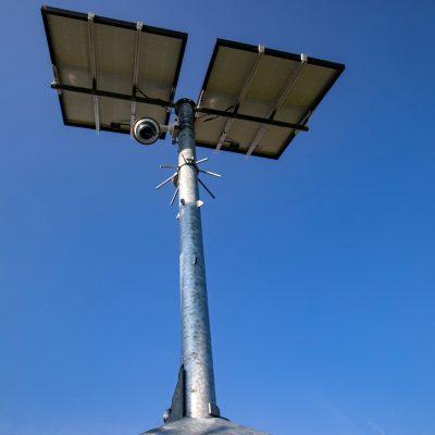 Sfeerbeeld van camerabeveiliging met een mobiele cameramast van onderaf te zien waardoor je de camera duidelijk onder de zonnepanelen ziet hangen.