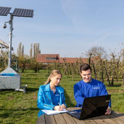 Sfeerbeeld van camerabeveiliging met een mobiele cameramast met zonnepanelen in een boomgaard. Op de voorgrond zitten een man en een vrouw aan een picknicktafel en kijken naar een laptop.