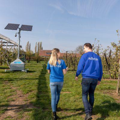 Sfeerbeeld van een mobiele cameramast in een boomgaard en een man en een vrouw in spijkerbroek en blauwe bovenkleding lopen er naar toe.