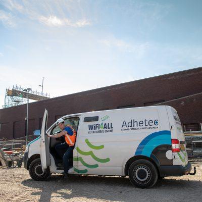 Sfeerbeeld van een witte bedrijfsbus met logo's van Adhetec en WiFi4ALL en een man die uitstapt.