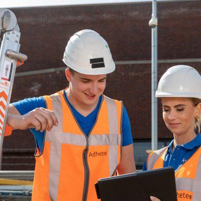 Sfeerbeeld van een man en een vrouw op een bouwplaats die samen naar een tablet kijken.