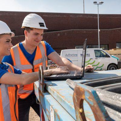 Sfeerbeeld van twee Adhetec medewerkers die op een bouwterrein het observatiesysteem controleren.